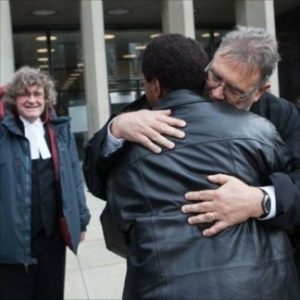 Photo shows Hay, foreground, hugging with one of his AIDWYC pro bono lawyers, Phil Campbell, immediately after the Nov 2014 court hearing. (Jesse Johnston photo)